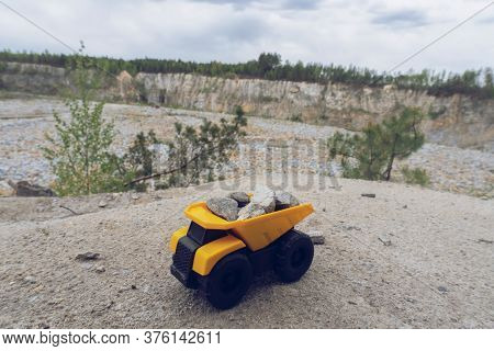 Small Yellow Car Toy, Mining Truck With Stones At The Hill At The Background Of Quarry, Toned, Copy