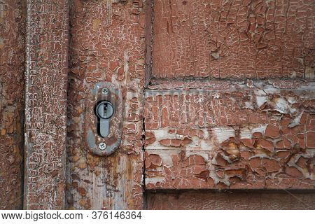 Close-up Texture Of Old Dark Wooden Entrance. Background Of Rough Distressed Door Leafs. Shabby Scra