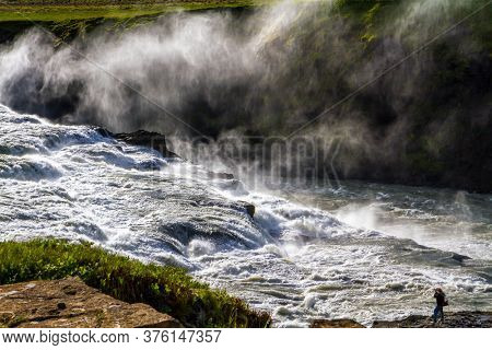 Iceland. Tourist - photographer with photo bag  takes pictures of burrowing waterfall. Gullfoss