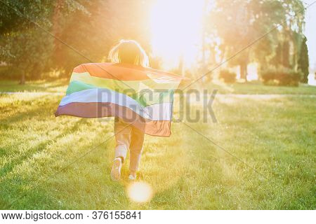 Back View Of Incognito Young Woman Swinging Rainbow Flag On Wind Behind Back. Unrecognizable Girl Ru