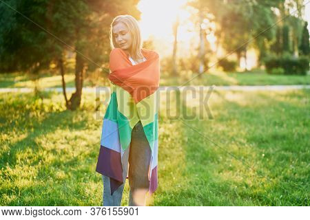 Young Tolerant Stunning Woman Wearing Jeans Posing In Park, Enjoying Summer Sunset On Background. Po