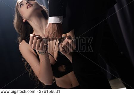 Dominant Man Touching Handcuffs On Submissive Woman In Underwear