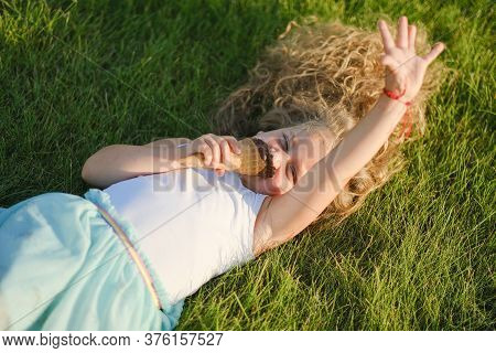 Little Blonde Girl With Long Hair Has Fun Eating Ice Cream In A Summer Park. Little Blonde Girl With
