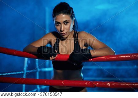 Professional Female Kickboxer With Strong Face Posing In Smoky Blue Atmosphere, Wearing Bandages On