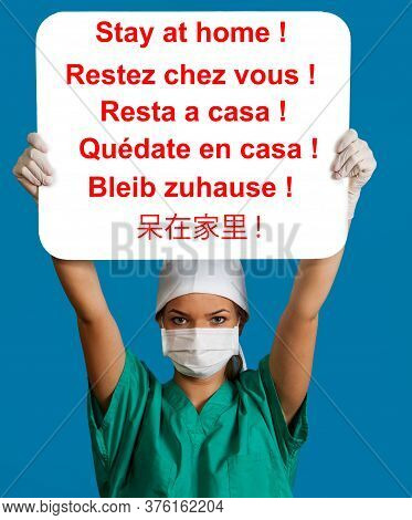 A Young Nurse In A Mask Holding A White Panel Above Her Head With The Six Languages Message Stay At