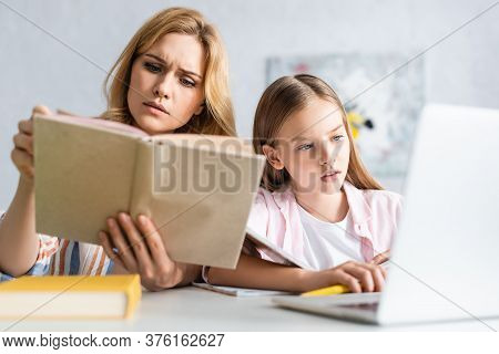 Selective Focus Of Concentrated Woman Reading Book Near Daughter Using Laptop At Table