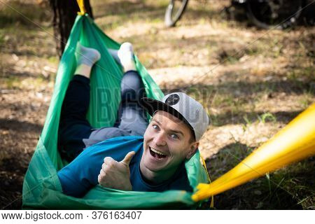 Young Happy Smiling Man In Hat Relaxing Outside In Hammock In Forest.