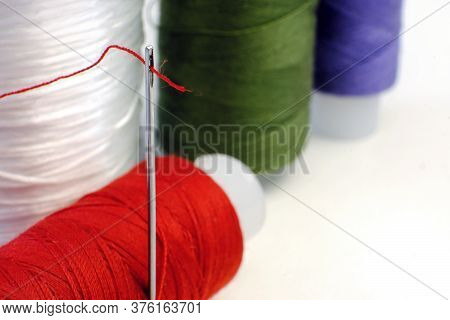 Spools Of Thread. Needle With Thread In The Eye Of The Needle.