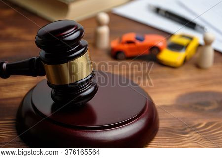 The Concept Of A Car Owner Accident Lawsuit. Judge Hammer Next To Car Models And Documents