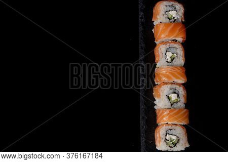 Philadelphia Roll With Salmon, Cheese And Cucumber On A Black Background. Sushi Philadelphia