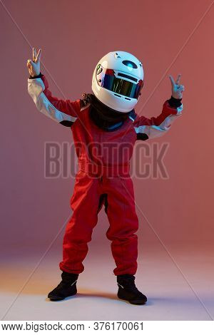 Cool Boy Child Racer In Helmet With Raised Hands With Peace Gesture, Standing In Neon Light. Kart Ra