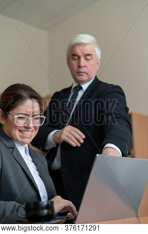 The Male Boss Indicates The Female Subordinate A Mistake. A Gray-haired Mature Business Man Scolds A
