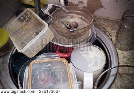 Dirty tableware in the sink in unwashed kitchen