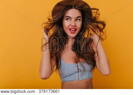 Shapely Lady With Trendy Bright Makeup Looking Away And Smiling. Indoor Portrait Of Easygoing Elegan