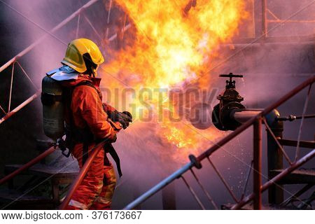 Firefighter using water fog type fire extinguisher to fighting with the fire flame from oil pipeline leak and explosion on oil rig and natural gas station. Firefighter and industrial safety concept.