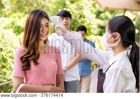 Asian waitress with face mask take temperature customer before getting in restaurant with social distance queue in line. Restaurant New normal restaurant concept after coronavirus covid-19 pandemic.