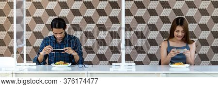 Panoramic two asian influencer food blogger or vlog take food photo at new normal social distance restaurant with table shield partition. Restaurant new normal lifestyle and food influencer concept.