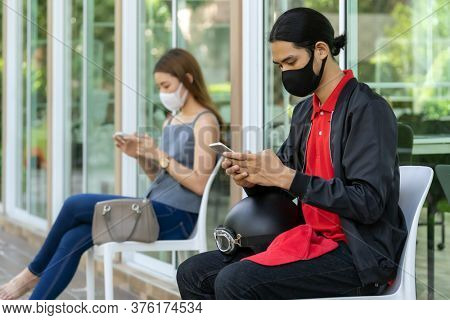 Asian customers wear face mask using mobile phone while sit in waiting social distance queue in front of restaurant with free copyspace for editing. New normal restaurant concept.