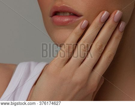Close-up Of Womans Lips With Fashion Pink Make-up And Manicure On Nails. Beautiful Female Full Lips