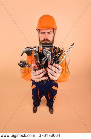 Builder Man. Serious Worker Holds Repair Tools. Building. Builder In Construction Helmet. Repairment