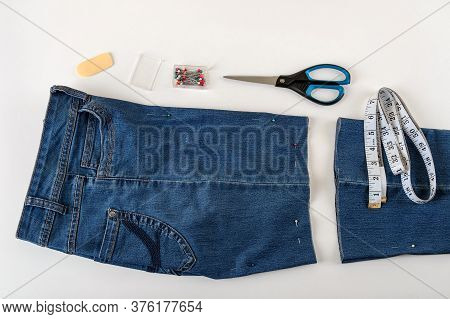 Just Cutted Blue Denip Shorts, Measuring Tape, Scissors And Sewing Pin On A White Table. Shorten The