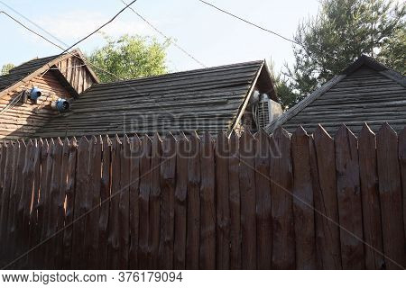 Part Of A Brown Wooden Wall From A Sharp Picket Fence In Front Of Gray Rural House Roofs