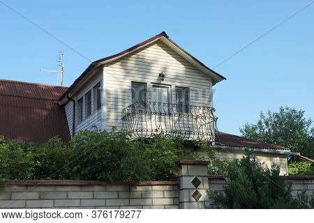 One Brown Iron Balcony In The White Attic Of A Private House With A Brown Roof Overgrown With Green