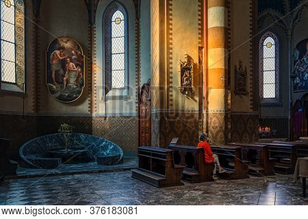 ALBA, ITALY - JUNE 14, 2020: Woman sitting on wooden pew inside of San Lorenzo - a Roman Catholic cathedral aka Duomo dedicated to Saint Lawrence in small town of Alba in Piedmont, Northern Italy.