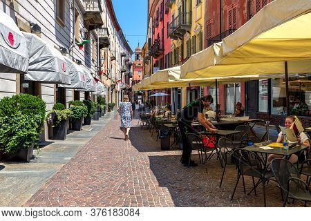ALBA, ITALY - JUNE 30, 2019: People in outdoor restaurant on narrow cobblestone street among colorful houses on Old Town of Alba - small town in Piedmont famous for white truffle and wine production.