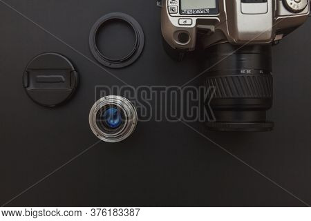 Photographer Workplace With Dslr Camera System And Lens On Dark Black Table Background. Hobby Travel