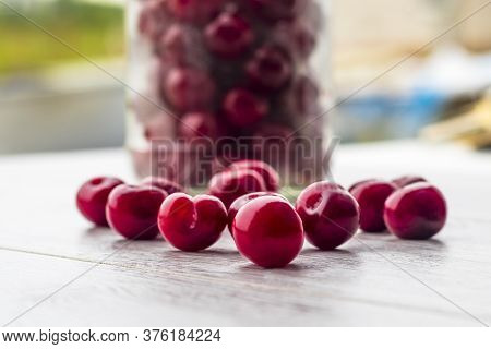 Fresh Collected Red Cherry In A Glass Jar. Berries Are Scattered On A Wooden Background