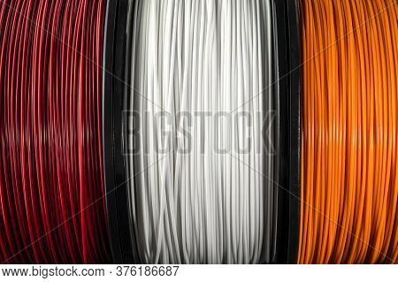 Three Coils Of Filament For 3d Printing. Bright Thermoplastic Of Red, White Smd Orange Colors. Reels