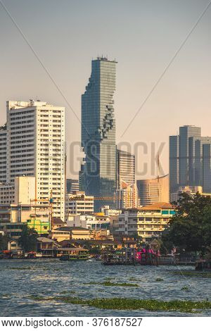 City Skyline As Seen From The Tourist Boat On Chao Phraya River At Sunset In Bangkok, Thailand
