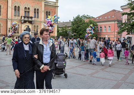 Novi Sad, Serbia - April 23, 2016: Two Old Women Passing By In Front Of A Crowd Of Kids And Young Ch