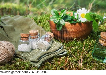 Three Bottle Of Homeopathic Globules, Infusion Bottle, Wooden Mortar Of Medicinal Herbs, Gloves On A