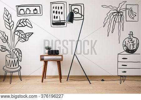Floor Lamp, Wooden Coffee Table And Clock With Blank Screen Near Drawn Plants, Paintings And Dresser