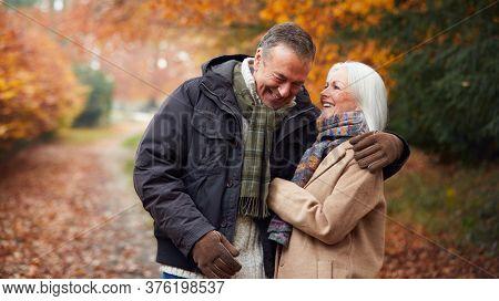 Loving Senior Couple Hugging As They Walk Along Autumn Woodland Path Through Trees