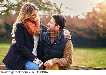 Loving Couple On Walk Through Autumn Countryside Sitting On Gate