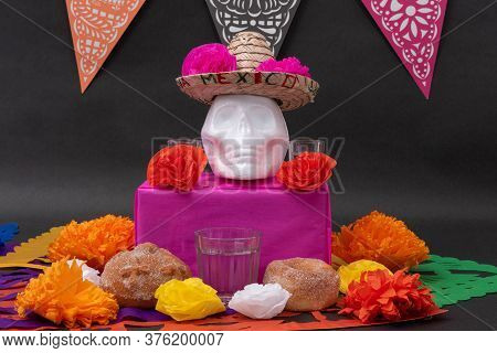 Mexican Day Of The Dead Altar With Traditional Bread, Colorful Flowers, A White Skull And Cut Paper