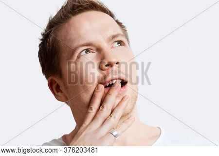 Contemplative young man with hand over mouth against white background