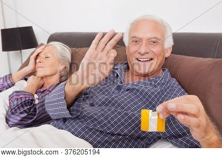 Portrait of excited elderly man holding torn condom packet while spouse sleeping behind on bed