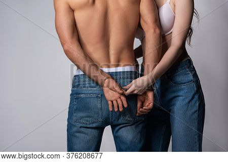 Cropped View Of Dominant Woman Touching Handcuffs On Submissive Man On Grey