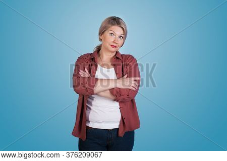 Interested Caucasian Senior Woman With Blonde Hair Posing With Crossed Hands On Blue Studio Wall Loo