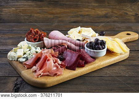 Italian Antipasto. Antipasti Board With Ham, Salsami, Prosciutto, Parmesan, Blue Cheese And Olives.