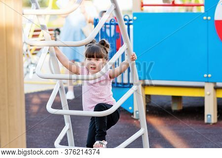 Child Playing On Outdoor Playground. Healthy Summer Activity For Children. Little Girl Climbing Outd
