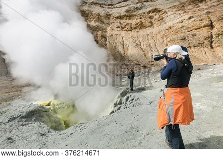 Woman Photographer Tourist Takes Pictures Of Volcanic Landscape, Hot Springs, Eruption Fumarole, Gas
