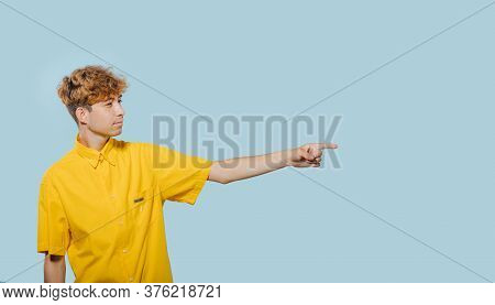 Teenage Boy Pointing With Finger In Side Direction In Studio On Blue Background, Teenager With Fashi