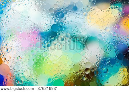 Close-up Of The Movement Of Oil Droplets On The Water Surface. Colorful Abstract Macro Background Of