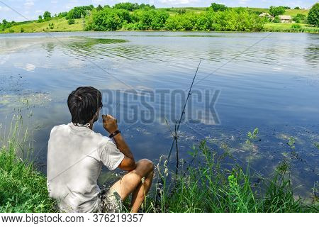 Man Sits Among Nature On The Shore Of A Pond Near A Fishing Rod - Back View. Young Adult Guy Fishes
