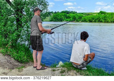 Two Adult Young Friends Fishing On The Shore Of A Lake. Fishermen With Fishing Rod In Comfortable Ca